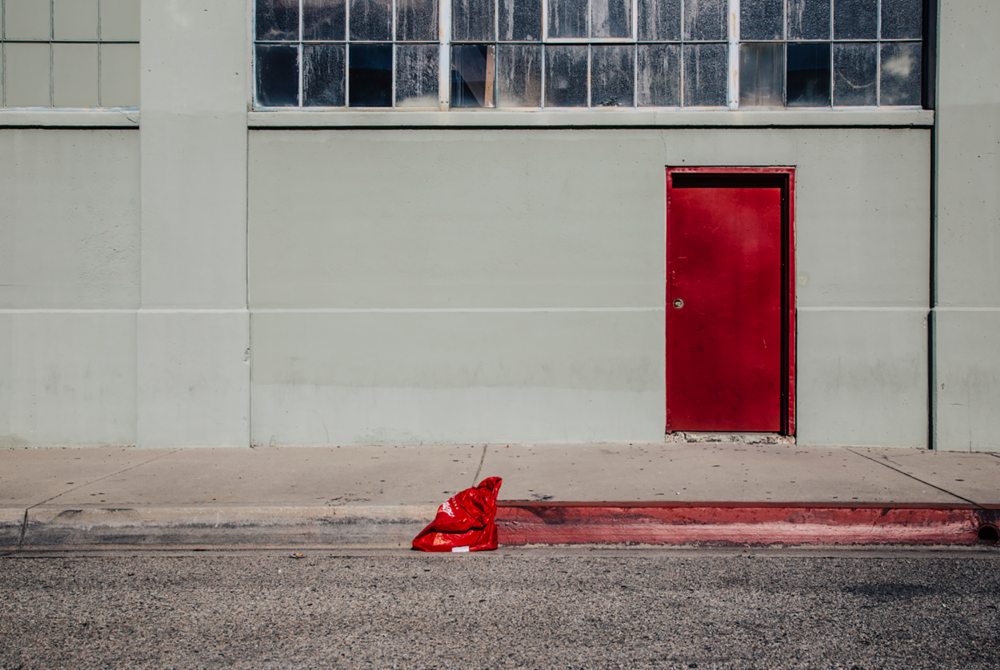 Minimal urban landscape photograph of architecture with a red door