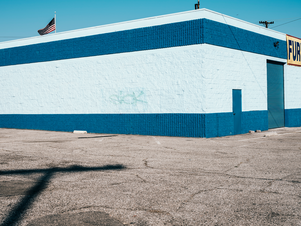 Minimal urban landscape photograph of architecture with the word sick spray painted on a blue building