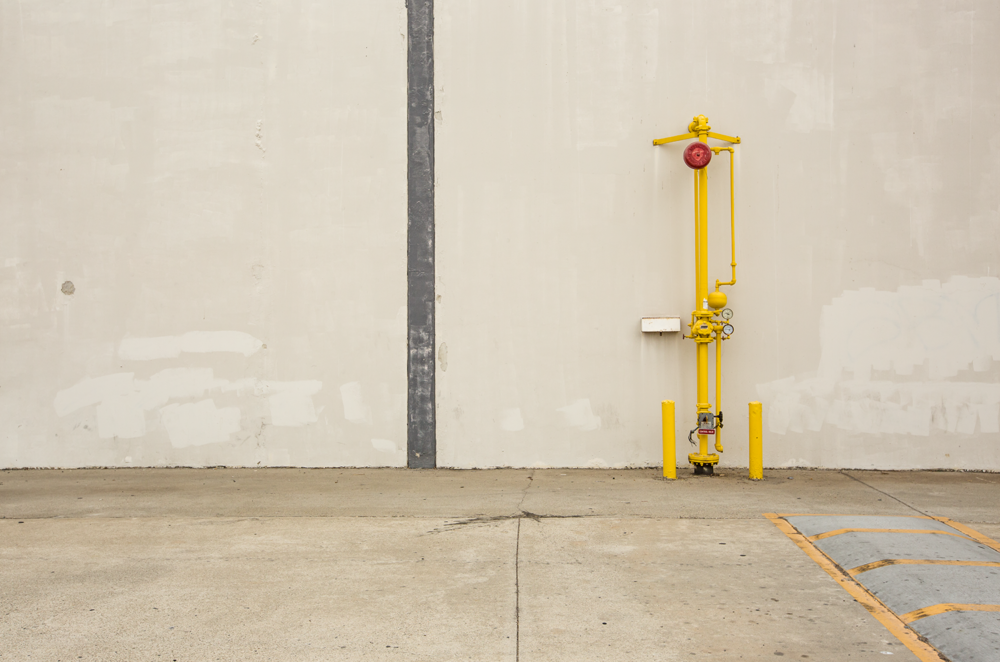 Minimal urban landscape photograph of architecture with a yellow pipe against a wall