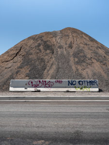Color photograph by Curtis Stage with a large dirt mound and a freeway divider